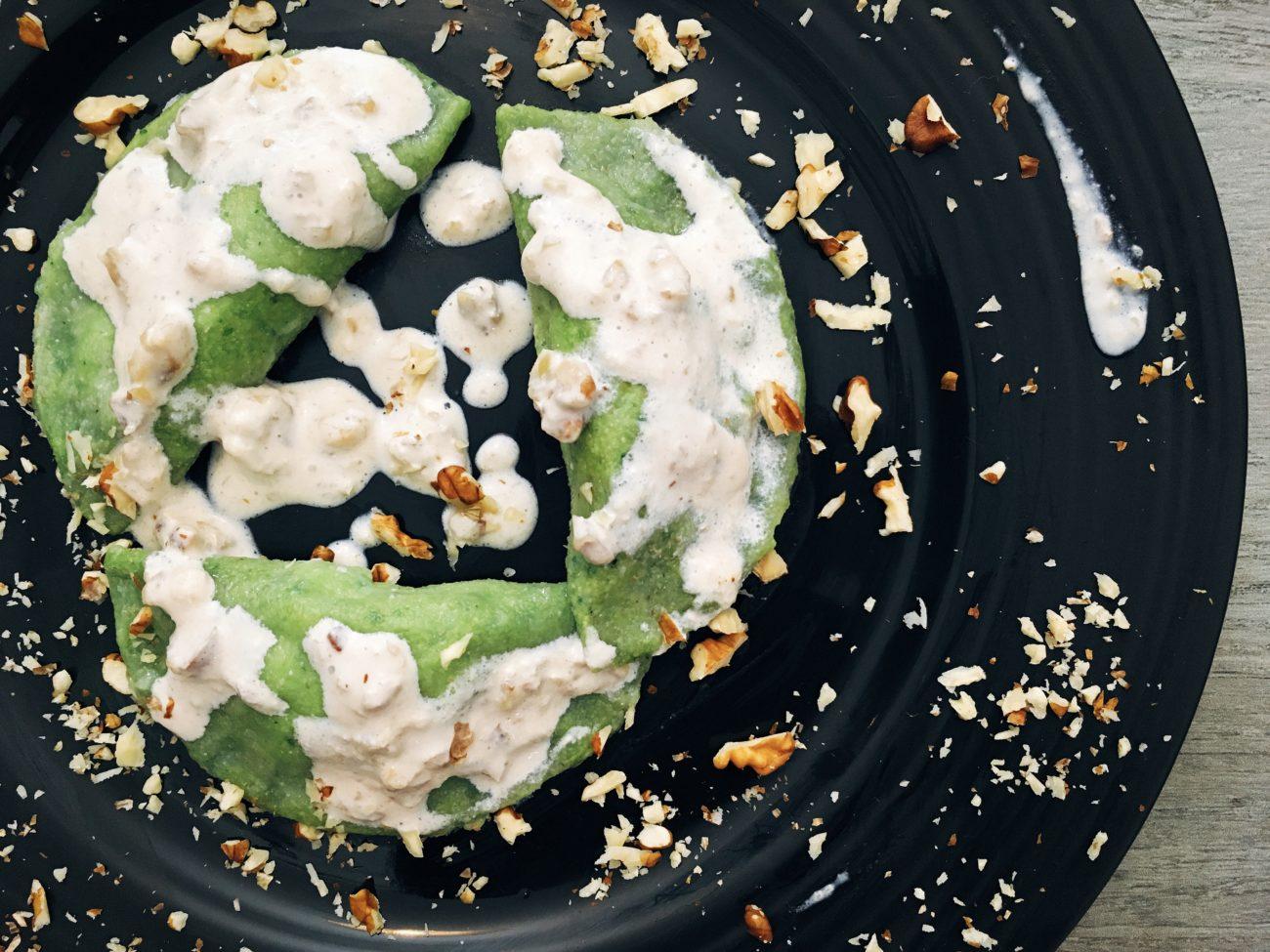 Ravioli verdi al ripieno di funghi conditi con panna e noci